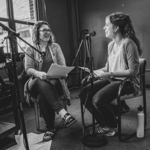 Two women at microphones reading from scripts. One is laughing.